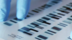 Scientist compares DNA profiles, tracking shot Stock Footage