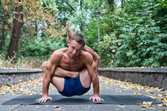 Handsome flexible Athletic man doing yoga asanas in the park Stock Photos