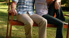 Couple relaxing in the park on bench Stock Footage