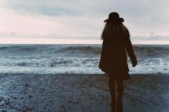 Woman in a black coat on the beach Stock Photos