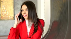 Brunette young business lady in red talking on iphone in cafe Stock Footage