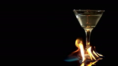Martini glass fire flames olvies slow motion black background title plate Stock Footage