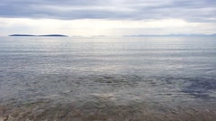 A dull sky above calm surf - stock footage