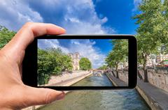 Male hand with smartphone taking a picture of Paris and Notre Dame. Tourism c Stock Photos