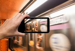 Female hand with smartphone taking a picture of New York subway train. Touris Kuvituskuvat