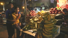 Indian teenage boys at a fruit stand of a busy street market. Stock Footage