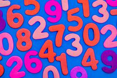 Mixed coloured numbers on a blue background. - stock illustration