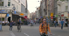 The Netherlands Amsterdam city life North Holland busy street cyclists bicycles Stock Footage