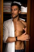 Sexy young man standing almost shirtless peering out of a walk in closet Stock Photos