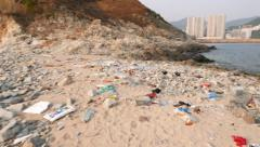 Trashed sandy beach, clean sea water, hillside and buildings on background Stock Footage