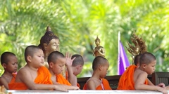 Young buddishm novice stayed around Buddha statue Stock Footage