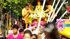 People spray holy water to the Buddha statue on parade Stock Footage