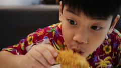 Little Asian child enjoys eating fried chicken . Stock Footage