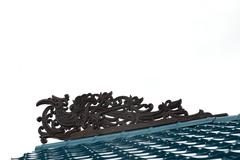 borneo traditional tribal carvings on the roof top of buildings - stock photo
