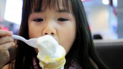 Stock Video Footage of little Asian girl enjoying her ice cream