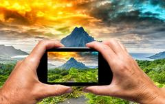 Man and woman hand capturing Polynesian Island landscape with smartphone - stock photo