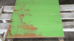 Carpenter use brush paint green color for coating wood board Stock Footage