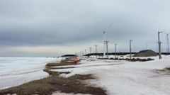 Engineer walks towards Windmills turning in winter Stock Footage