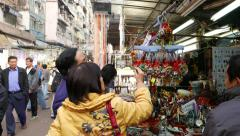 Old chinese couple chooses amulet on the market Stock Footage