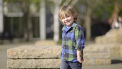 Happy Little Boy Walks Around Rock Sculptures In A City Park, Happy To Explore Stock Footage