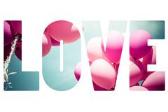 Word LOVE over pink balloons. Stock Photos