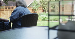 Senior African couple sitting on porch drinking coffee talking Stock Footage