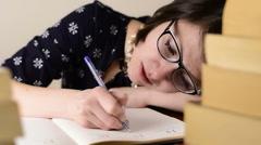 Black glasses woman sleep, work on a wood desk behind of books Stock Footage
