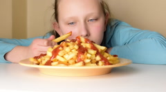 Blonde hungry teenage girl looking, eating  french fries from dish on table - stock footage
