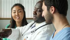 Diverse Medical team consulting with tablet and looking pleased - stock footage