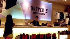 Shopper line up at check out counter inside Forever 21 store Stock Footage