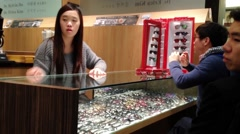 Female optician guides and assists male to choose a new pair of glasses Stock Footage
