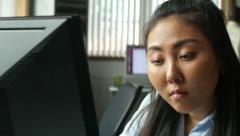 Young Asian professional working on computer in modern office - stock footage