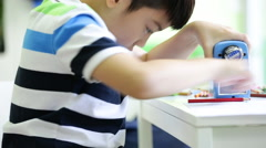 Little asian child sharpens pencil with shapes for draw Stock Footage
