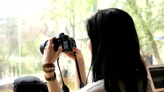 Brunete girl photographer reviews photos snapshots on camera Stock Footage