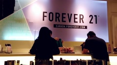 Shopper line up at check out counter inside Forever 21 store - stock footage