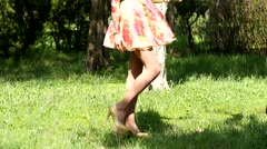 Sexy girl legs walking in park on high hills Stock Footage
