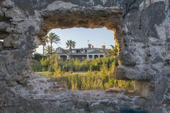 House seen through the hole of a ruined wall - stock photo