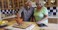 Senior African couple eating fresh baked cookies - stock footage