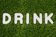 Drink text made of white wood design element on grass background. - stock photo