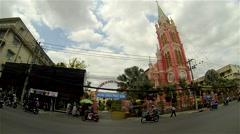Ho Chi Minh City - April 2015: Street view with motorbike traffic and church. Stock Footage