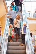 Mother And Children On Escalator In Shopping Mall Stock Photos