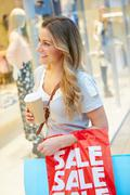 Female Shopper With Takeaway Coffee In Mall - stock photo