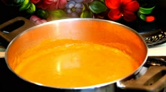 Pumpkin based soup  being cooked in a pot on the stove Stock Footage