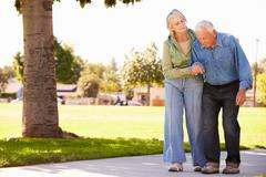 Senior Woman Helping Husband As They Walk In Park Together Stock Photos