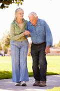 Senior Woman Helping Husband As They Walk In Park Together - stock photo