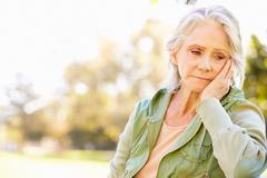 Depressed Senior Woman Sitting Outside Stock Photos