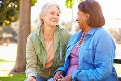 Two Senior Women Talking Outdoors Together Stock Photos