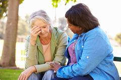 Woman Comforting Unhappy Senior Friend Outdoors - stock photo
