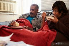 Senior Couple With Poor Diet Keeping Warm Under Blanket Stock Photos