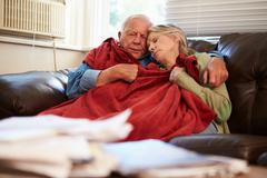 Senior Couple Trying To Keep Warm Under Blanket At Home Stock Photos